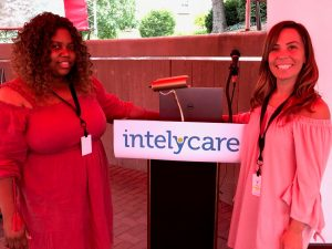IntelyCare nurses smiling while standing at a podium during the welcome event in Cincinnati