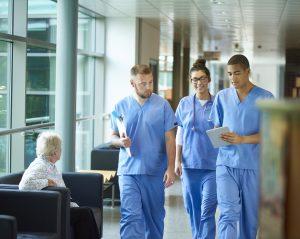 three nurses walk together down a corridor