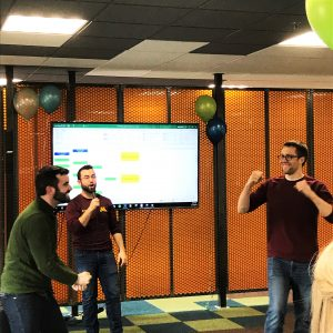 Corey announces the rock paper scissor championship match at the company celebration
