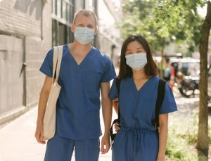 Two IntelyPro per diem nurses wearing masks on the street after attending covid-19 nurse training